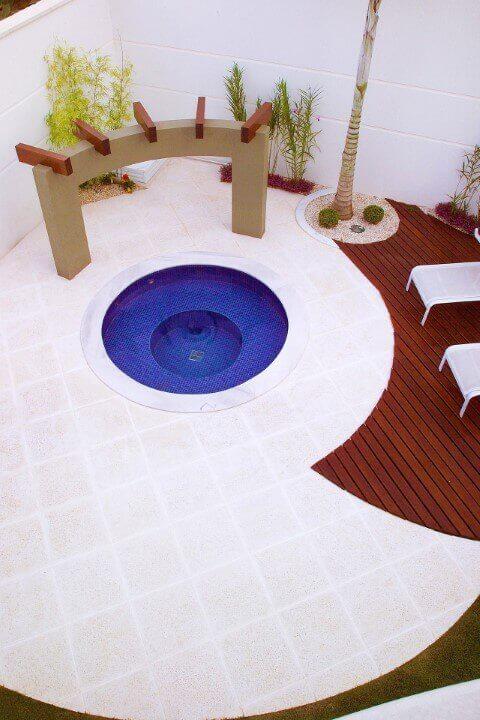 O recorte do deck em madeira traz um contraste interessante para a piscina redonda pequena. Projeto de Aquiles Nicolas Kilaris