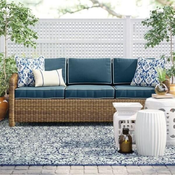 O sofá de vime e o garden seat branco criam uma atmosfera aconchegante no terraço