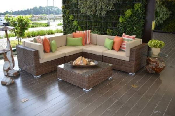 O sofá de vime em formato L otimiza o espaço do ambiente