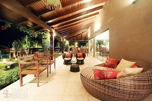O sofá redondo de vime traz conforto e charme para esse terraço