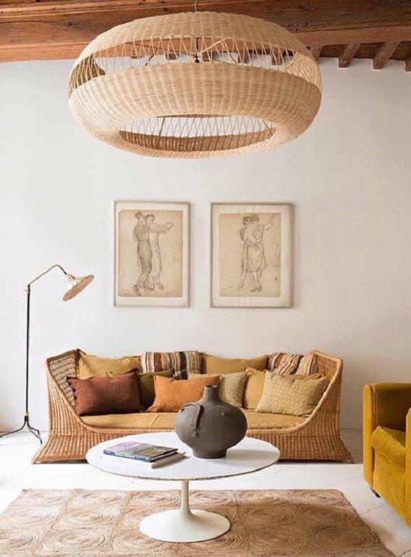 O teto de madeira se harmoniza com a decoração da sala com sofá de vime