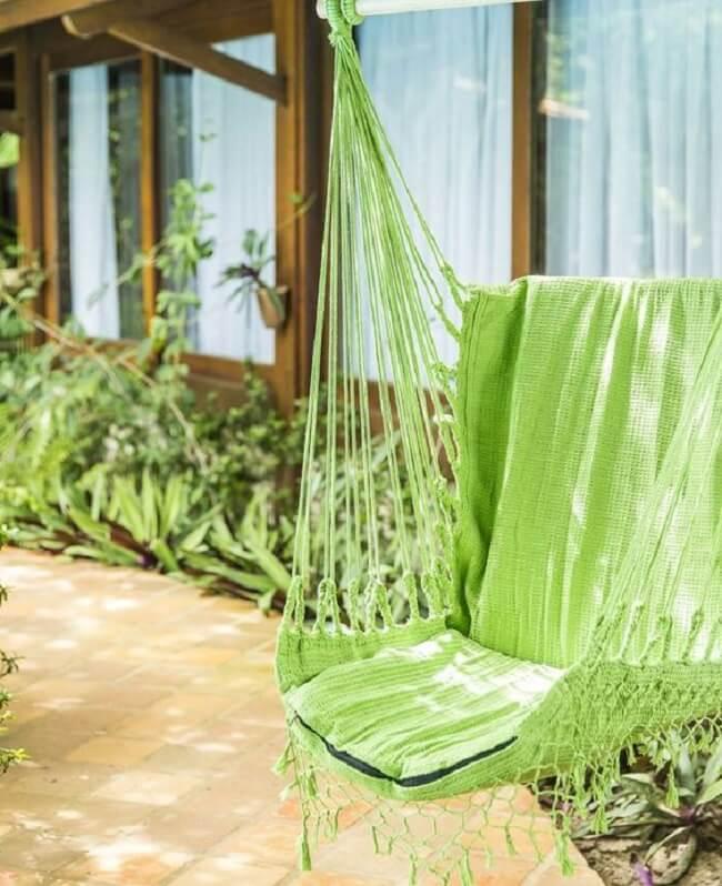 O tom verde da cadeira de balanço rede se mistura com as plantas do jardim