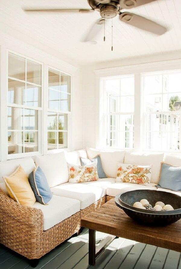 O ventilador de teto traz frescor para a sala com sofá de vime