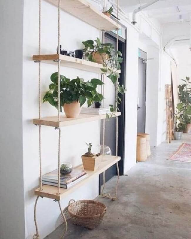 Os vasos de plantas realçam a beleza da prateleira de corda e madeira. Fonte: Fashionismo