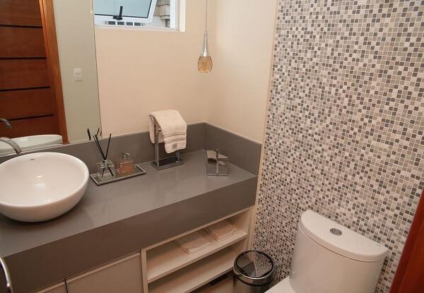 Pastilhas de vidro na parede e silestone cinza na bancada decoram o banheiro