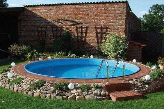 Pedras, plantas e tijolos decoram o entorno da piscina de fibra redonda. Fonte: Arkpad