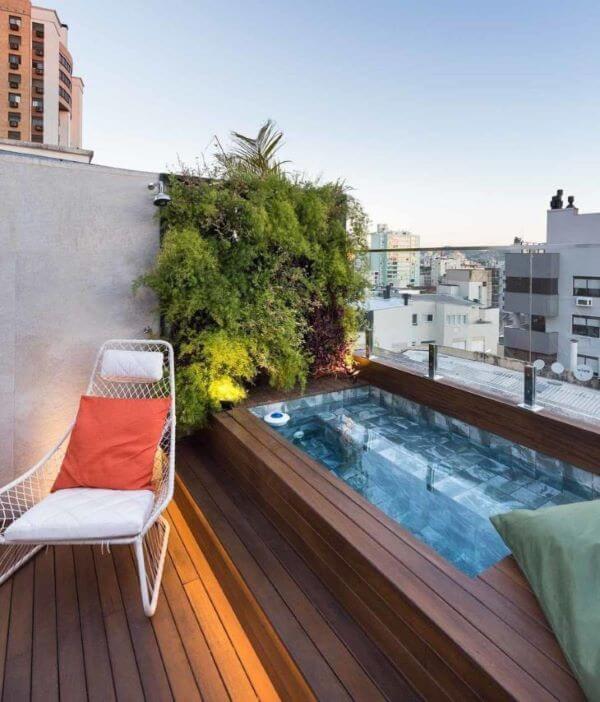Piscina elevada com jardim vertical e poltrona de balanço