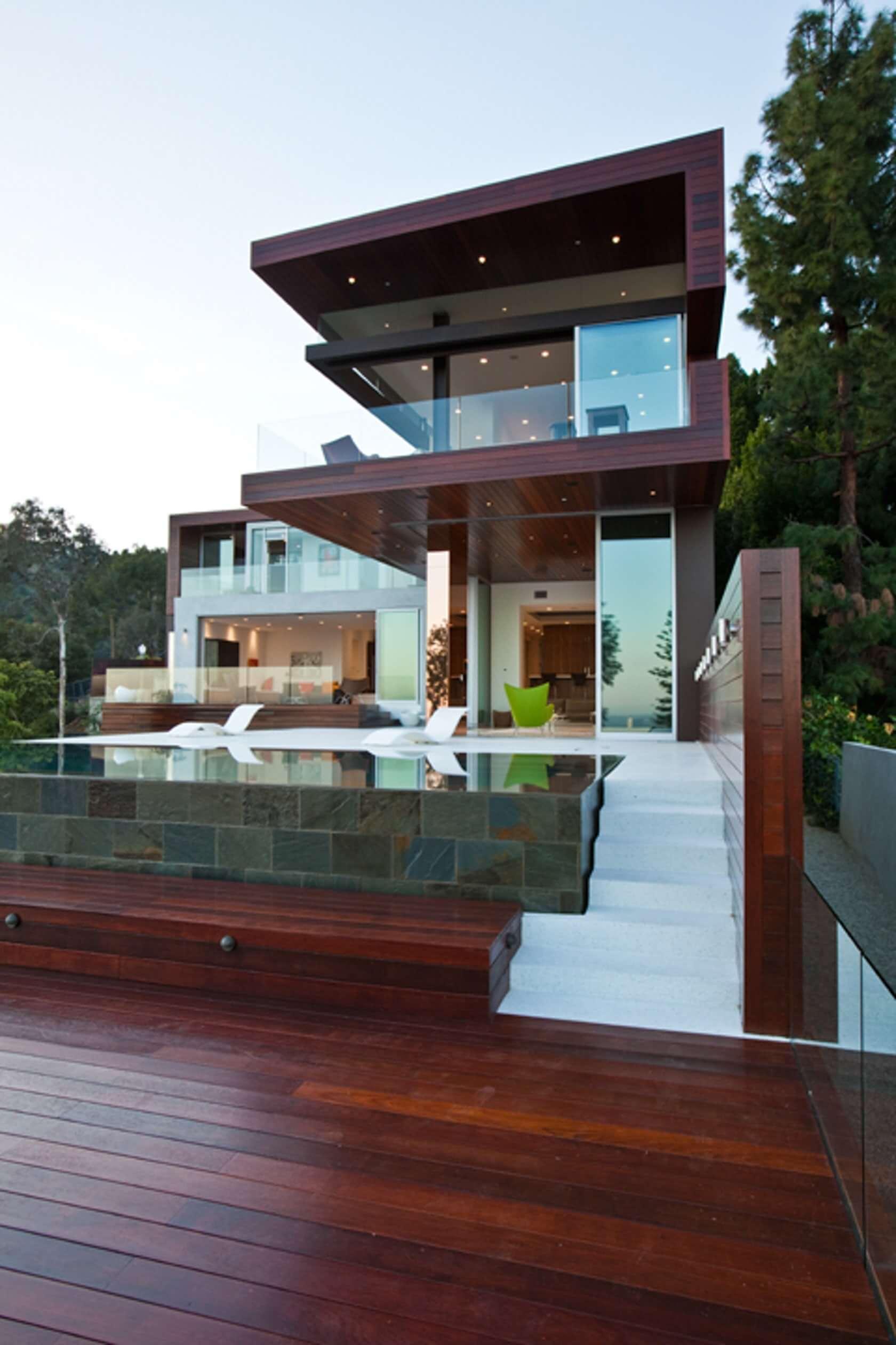Piscina elevada de vidro e deck de madeira