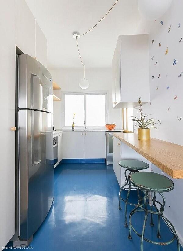 Piso colorido cozinha azul, armários brancos e bancada de madeira formam uma linda composição