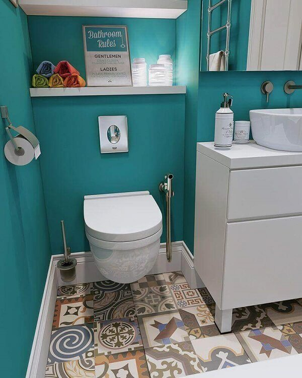 Piso colorido em ladrilho hidráulico e marcenaria branca decoram o banheiro