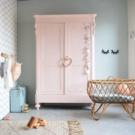 Quarto de bebe retro com guarda roupa rosa e berço de vime