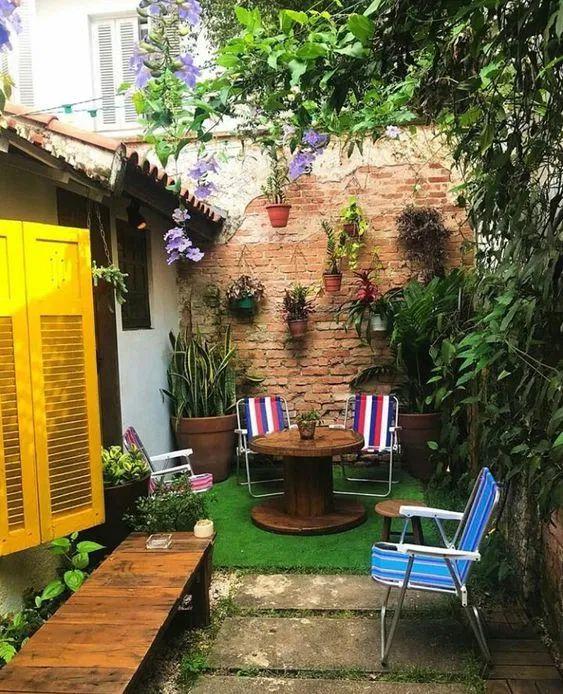 Quintal pequeno com jardim e mesas para relaxar