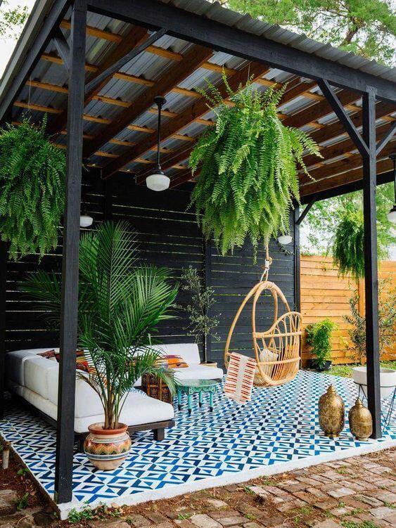 Quintal pequeno com pergolado plantas e sofás