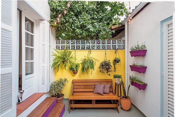 Quintal pequeno com plantas e sofa de madeira