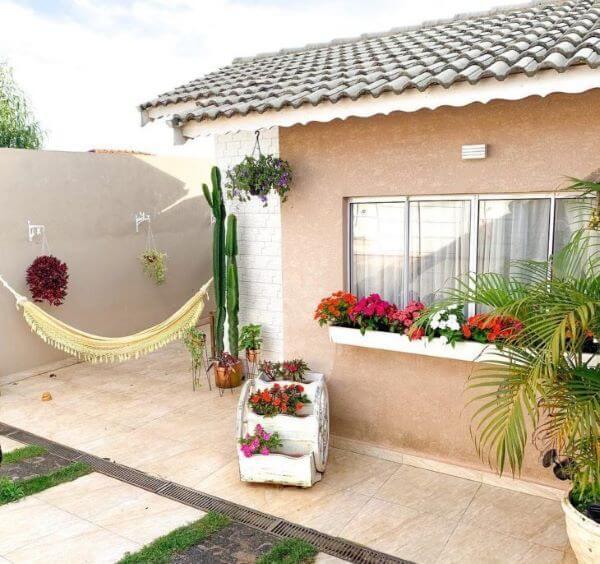 Quintal pequeno decorado com flores e rede de descanso