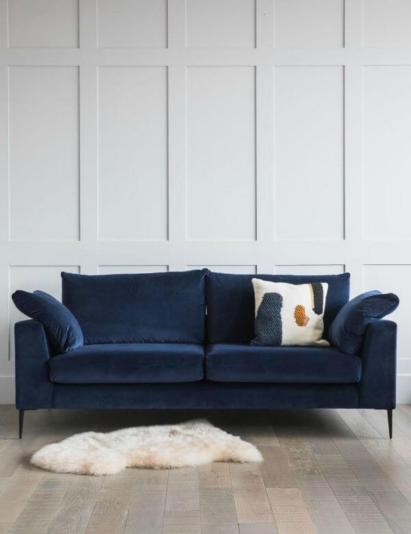 Sala Branca com sofá azul marinho e almofada