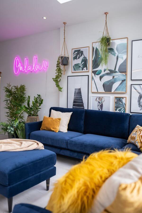 Sala branca com sofá azul marinho e enfeites amarelos