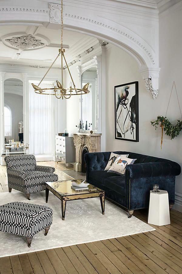 Sala branca com sofá azul marinho e poltrona preto e branco