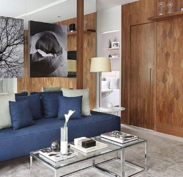 Sala chique com revestimento de madeira e sofá azul marinho