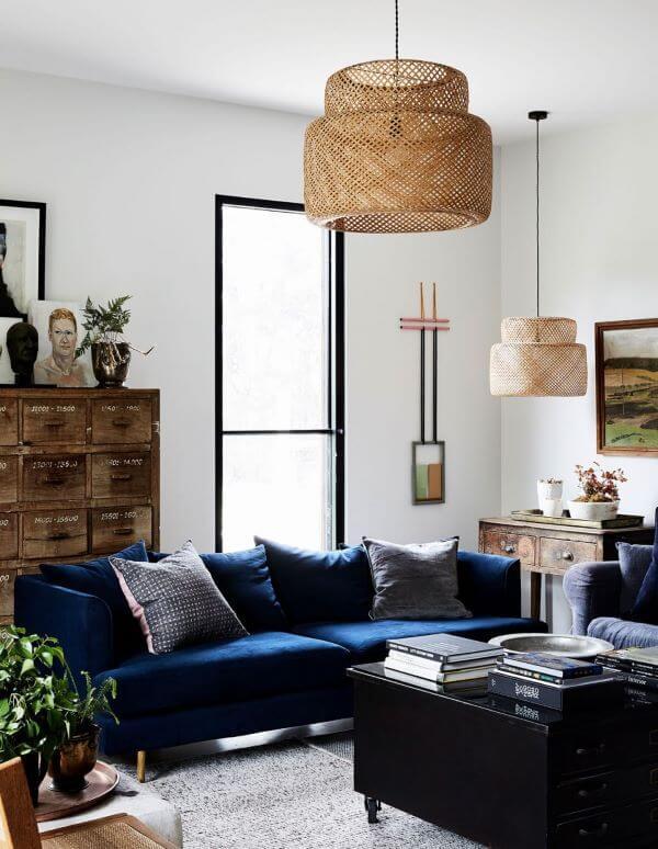 Sala clara com sofá azul marinho e lustre rustico