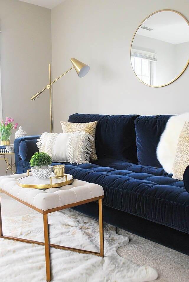 Sala clara com sofá azul marinho em destaque