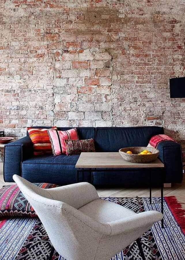 Sala com parede de tijolinho rustico e sofá azul marinho