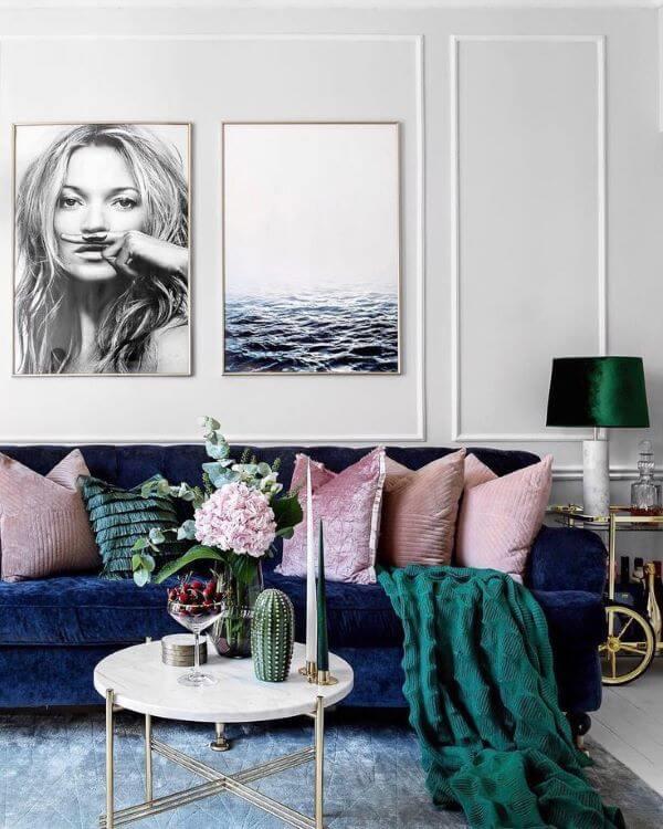 Sala com sofá azul marinho almofadas e rose e manta