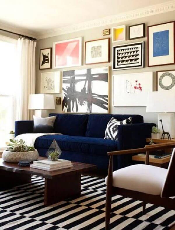 Sala com sofá azul marinho e conjunto de quadros na parede