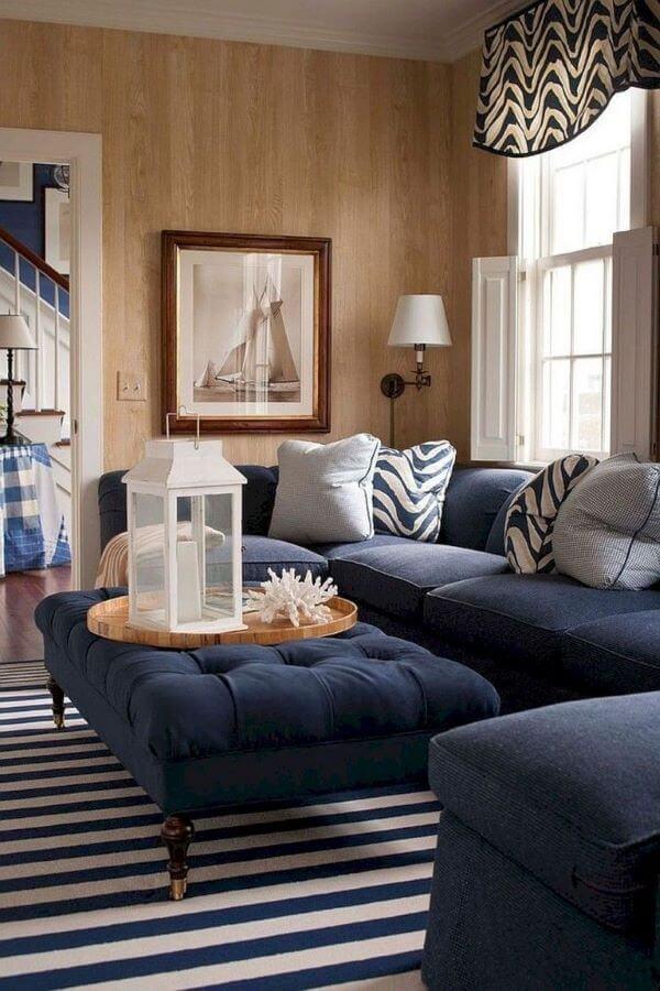 Sala com sofá azul marinho e puff na mesma cor