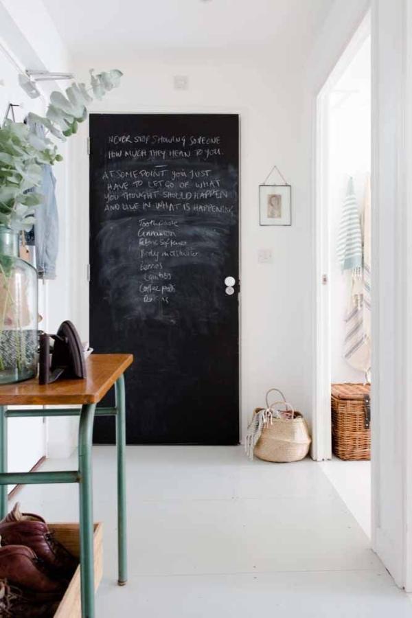 Sala de estar com porta de entrada pintada de tinta lousa preta