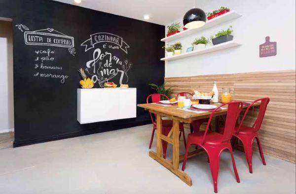 Sala de jantar com tinta lousa preta e cadeiras vermelhas