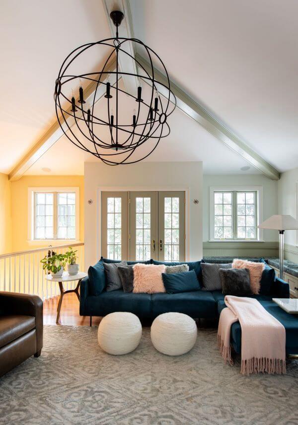 Sala grande com sofá azul marinho em L e manta rosa claro