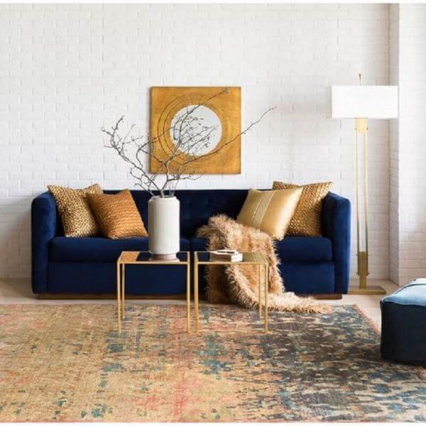 Sala moderna com sofá azul marinho e enfeites dourados
