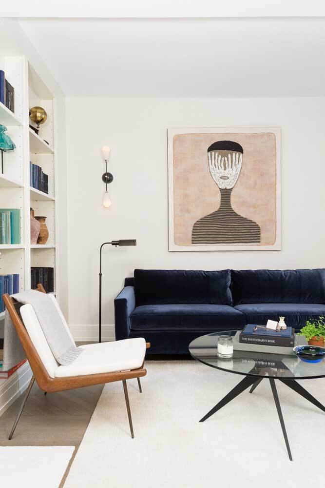 Sala moderna com sofá azul marinho e móveis brancos