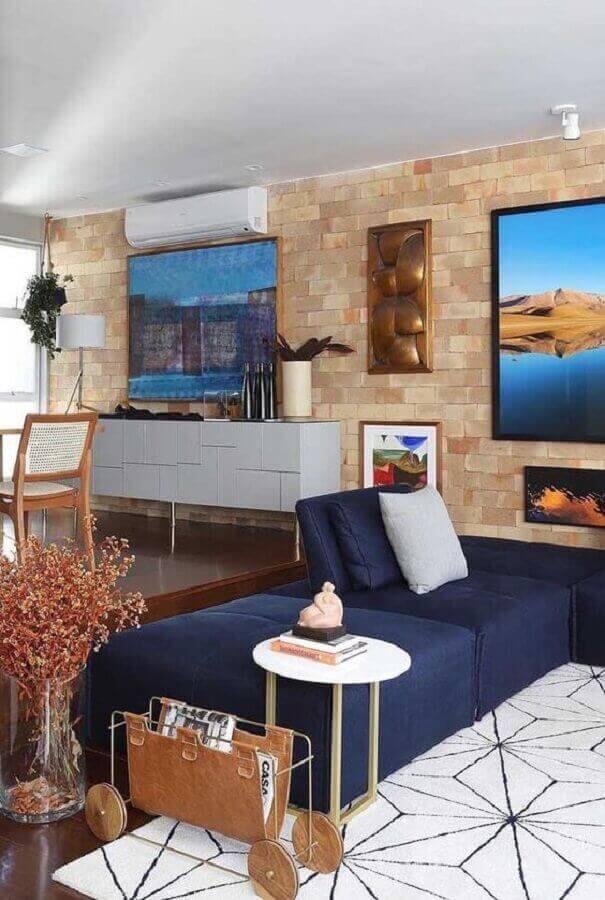 Sala moderna com sofá azul marinho e parede de tijolinho