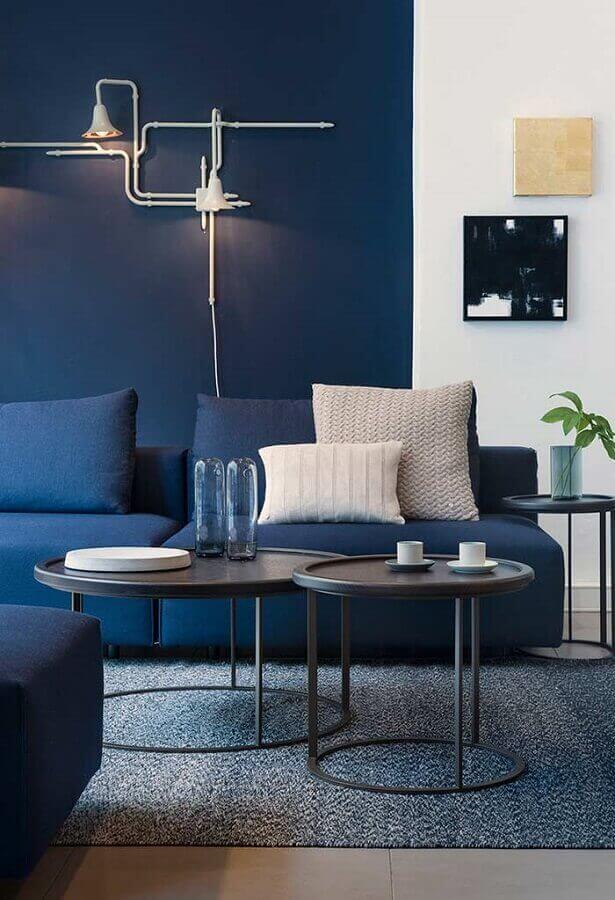 Sala moderna com sofá azul marinho e pintura setorizada na parede