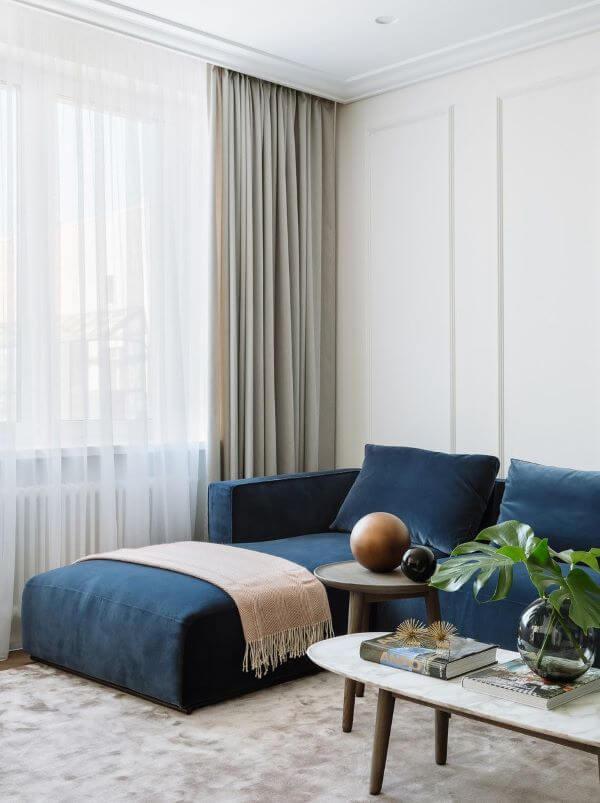 Sofá azul marinho com manta rosa