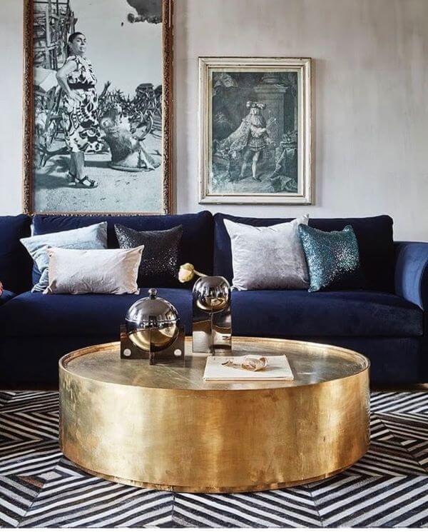 Sofá azul marinho com mesa de centro dourada