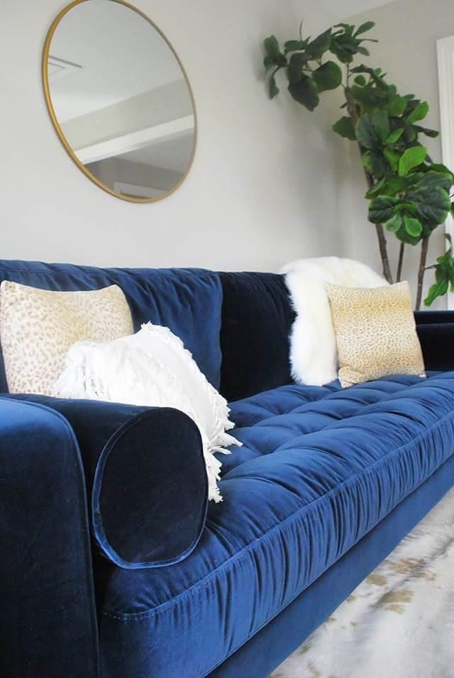 Sofá azul marinho de veludo com almofadas brancas