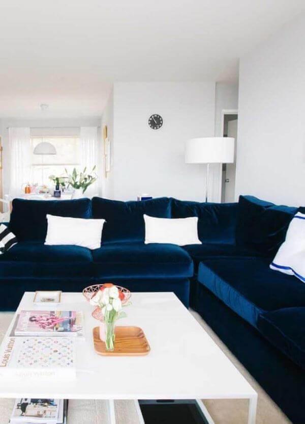 Sofá azul marinho em L com almofadas brancas