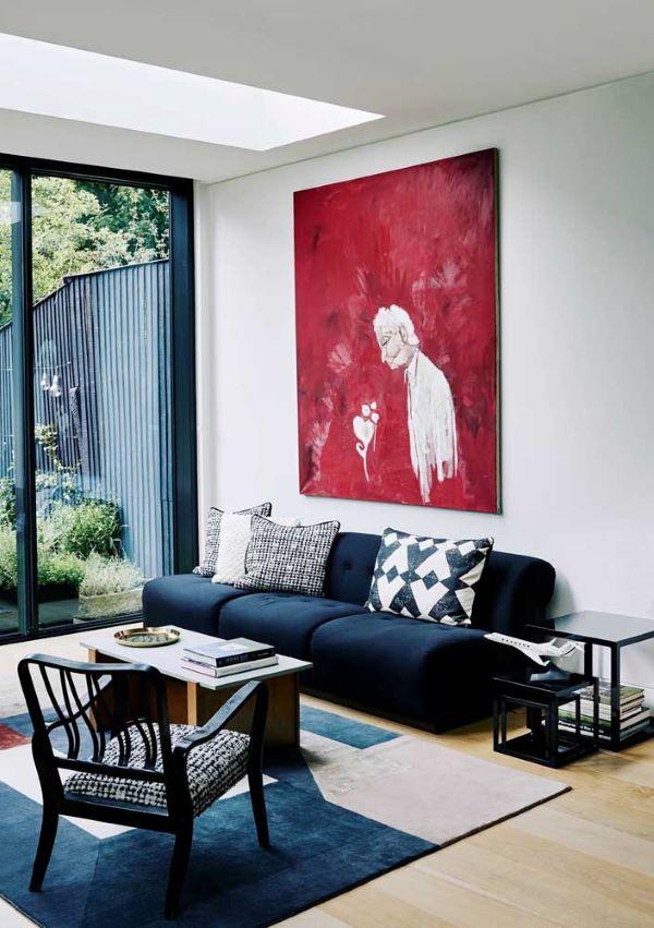 Sofá azul marinho na sala branca com quadro vermelho