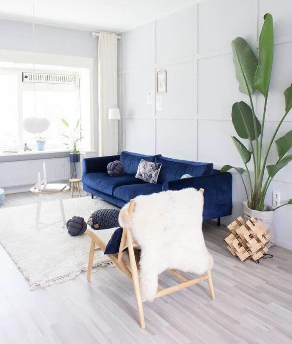 Sofá azul marinho na sala branca e clara