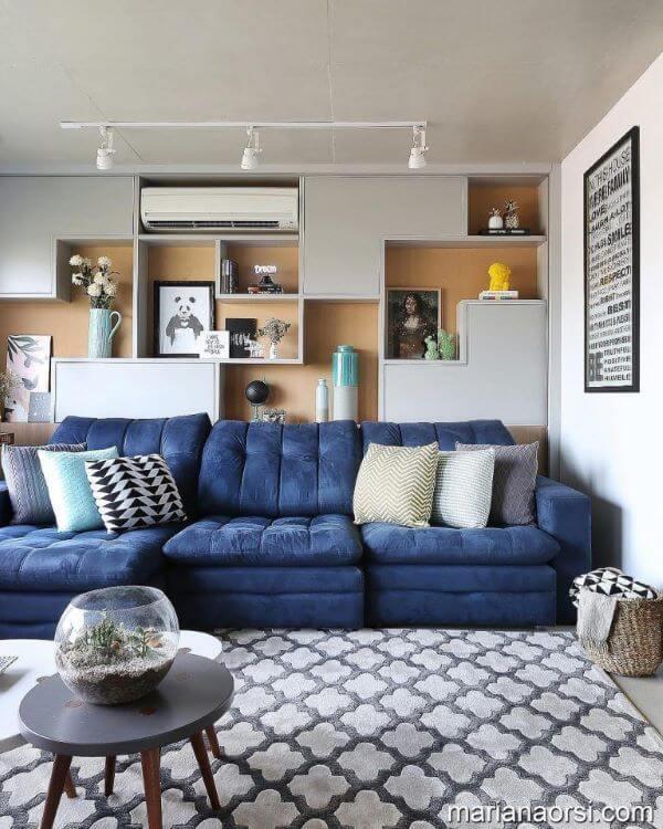 Sofá azul marinho na sala moderna com tapete estampado cinza