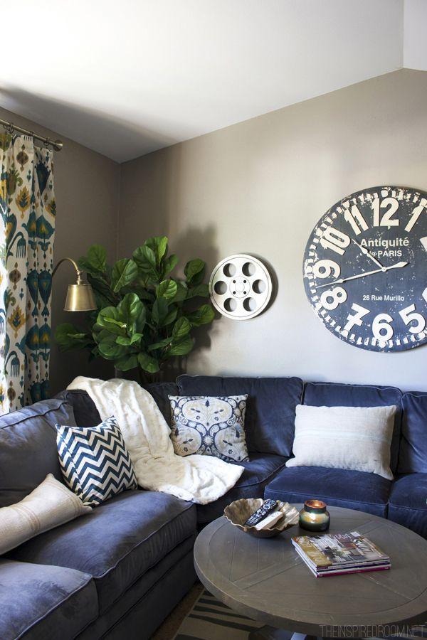 Sofá de canto azul marinho com quadros modernos