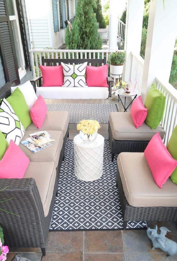 Tons de rosa e verde invadem a decoração dessa varanda com sofá de vime