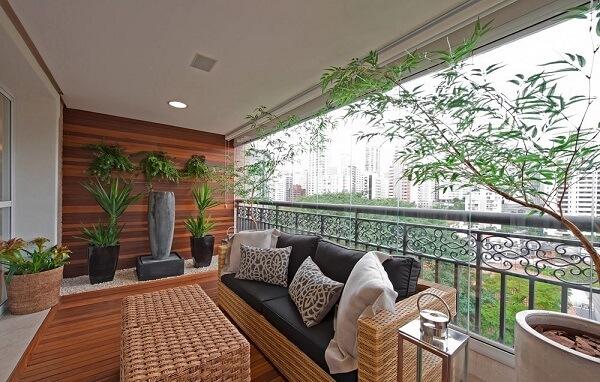 Varanda ampla decorada com um lindo sofá de vime e vasos de plantas
