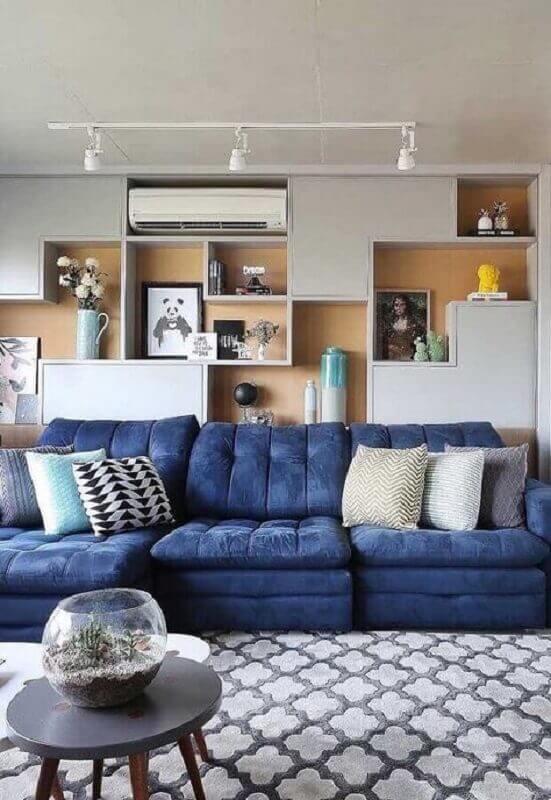 almofadas diferentes para sala de TV moderna decorada com sofá azul e parede de nichos Foto Pinterest