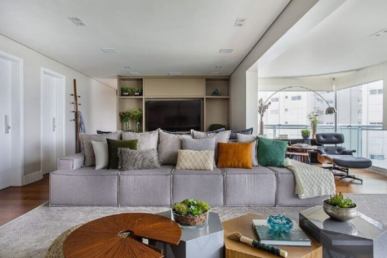 almofadas diferentes para sala grande moderna integrada com varanda de apartamento Foto Tria Arquitetura