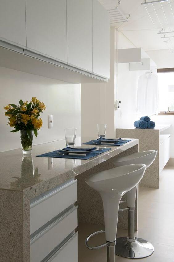 Bancada de cozinha em granito bege com bancos brancos para cafe da manhã