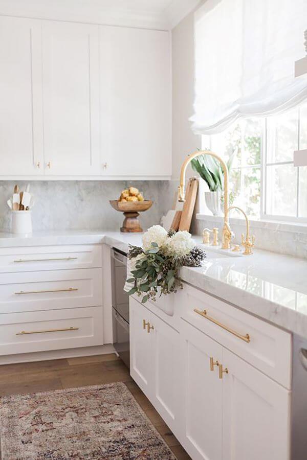 Bancada de cozinha branca com armários da mesma cor e torneira dourada gourmet
